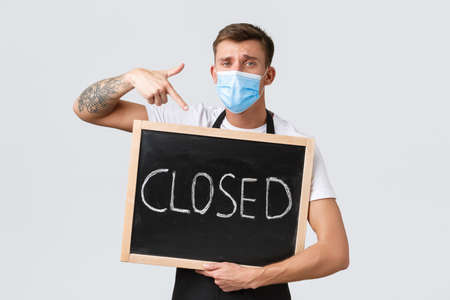 Small retail business owners, covid-19 and social distancing concept. Disappointed and sad salesman in medical mask, barista showing closed sign, inform clients restaurant not working Stock fotó