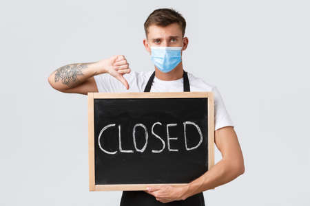 Small retail business owners, covid-19 and social distancing concept. Disappointed sad barista, waiter in medical mask showing thumbs-down as inform clients restaurant closed, white background