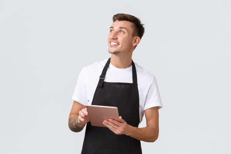 Small business, coffee shop and cafe employees concept. Friendly charismatic blond guy, barista or waiter in black apron, looking upper left corner delighted, holding digital tablet, taking orders