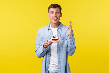 Celebration, holidays and people emotions concept. Hopeful man celebrating birthday, cross fingers good luck while making wish on b-day cake with lit candle, standing dreamy over yellow background