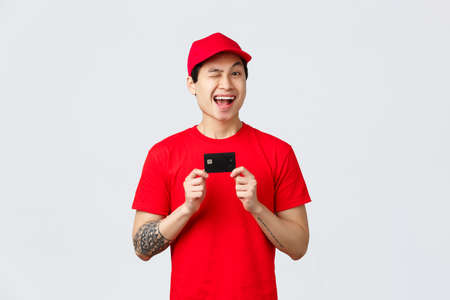 Friendly smiling asiand elivery man in red cap and t-shirt uniform, wink cheerful, recommend using credit card, buy contactless during virus outbreak. Courier give advice order online on coronavirus