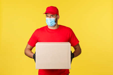 Express delivery during pandemic, covid-19, safe shipping, online shopping concept. Indecisive or suspicious courier feel disbelief, reluctant give order box to wrong person, hold package box Reklamní fotografie