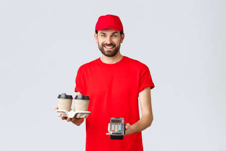 Food delivery, quarantine, stay home and order online concept. Friendly bearded courier in red uniform handing coffee delivery and POS terminal for client to pay contactless, grey background