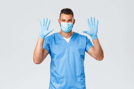 Healthcare workers, covid-19, coronavirus and preventing virus concept. Smiling friendly-looking and optimistic nurse, male doctor in medical mask and scrubs, showing empty hands in gloves 免版税图像 - 151048727