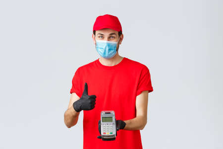 Contactless delivery, payment and online shopping during covid-19, self-quarantine. Friendly smiling courier in red uniform cap, t-shrit, medical mask and gloves, advice pay order with POS terminal