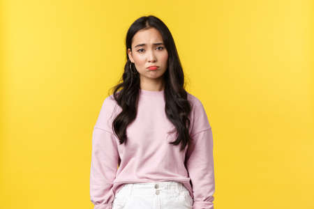 People emotions, lifestyle and fashion concept. Depressed and sad, gloomy korean girl pouting, looking down in dumps, feeling upset and displeased, standing yellow background