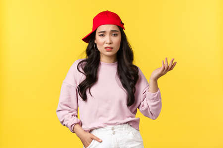 People emotions, lifestyle leisure and beauty concept. Skeptical and unimpressed stylish korean girl in red cap, raising hand say so what, feel unbothered and careless, yellow background