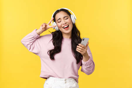 People emotions, lifestyle leisure and beauty concept. Carefree good-looking asian woman close eyes and dancing relaxed with smartphone, listening music in headphones, singing karaoke
