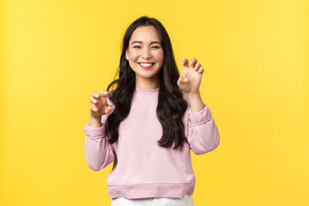 People emotions, lifestyle leisure and beauty concept. Cute and silly smiling, playful asian girl making cat paws and grinning adorable, fool around, acting like tiger coquettish, yellow background