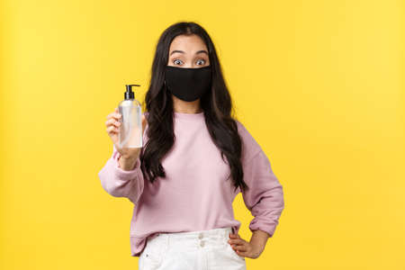 Covid-19, social-distancing lifestyle, prevent virus spread concept. Surprised asian girl in face mask always using hand sanitizer during coronavirus pandemic, recommend hygiene product 版權商用圖片