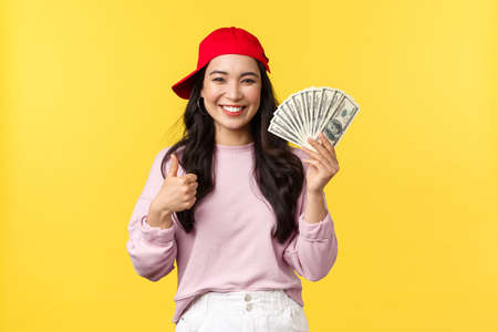 People emotions, lifestyle leisure and beauty concept. Cheerful and upbeat smiling korean girl in hip hop cap, showing thumbs-up and cash, explain how earn money on freelance, yellow background Reklamní fotografie