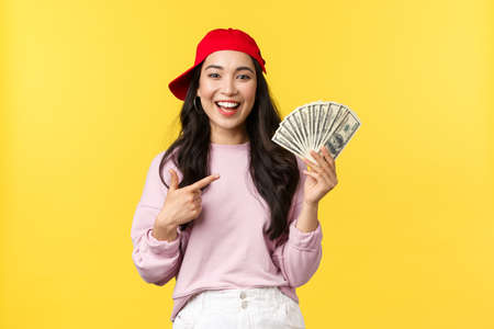 People emotions, lifestyle leisure and beauty concept. Enthusiastic smiling asian woman showing money, pointing at cash and looking pleased as earned first payment at new job, wear red cap