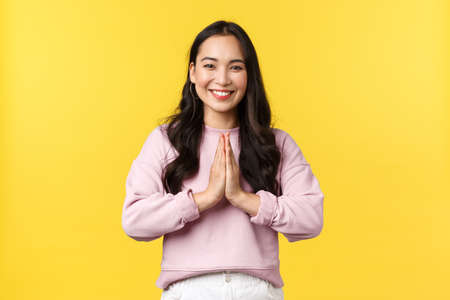 People emotions, lifestyle and fashion concept. Pleasant good-looking asian girl hold hands in pray and smiling friendly, bowing polite to greet person, say namaste, standing yellow background