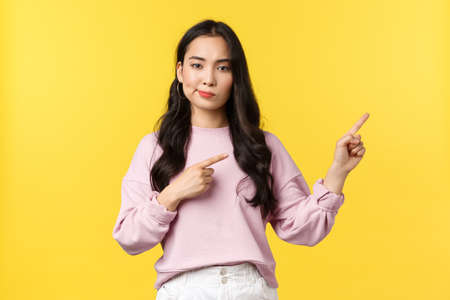 People emotions, lifestyle and fashion concept. Skeptical unimpressed asian woman smirk and looking unbothered as pointing fingers right, standing yellow background 版權商用圖片