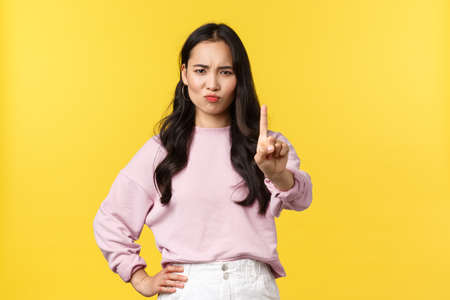 People emotions, lifestyle and fashion concept. Not so fast. Serious-looking confident asian girl denying something, shaking finger in disapproval, rejecting or prohibit offer 版權商用圖片