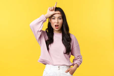 Lifestyle, emotions and advertisement concept. Arrogant and sassy confident young asian woman mocking person for losing, showing loser sign on forehead, stand yellow background 版權商用圖片