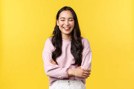 People emotions, lifestyle and fashion concept. Cheerful good-looking korean girl having fun, laughing out loud and feeling happy, standing joyful over yellow background