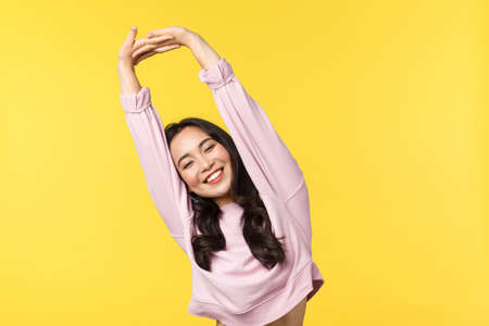 Lifestyle, emotions and advertisement concept. Cute and silly asian woman stretching and tilting body after good nap or sleep, smiling with closed eyes, feeling relaxed and happy, yellow background