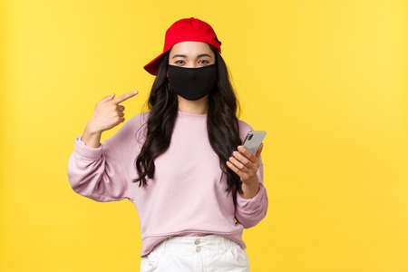 Covid-19, social-distancing lifestyle, prevent virus spread concept. Smiling cute asian girl pointing at face mask, asking protect health during coronavirus, holding mobile phone, yellow background