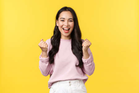 Lifestyle, emotions and advertisement concept. Cheerful and excited cute asian girl winning lottery, feel luck and upbeat, triumphing over achievement, say yes and fist pump rejoicing