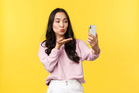 People emotions, lifestyle leisure and beauty concept. Stylish and flirty asian girl taking photo for social media, make selfie, sending air kiss at smartphone camera, stand yellow background