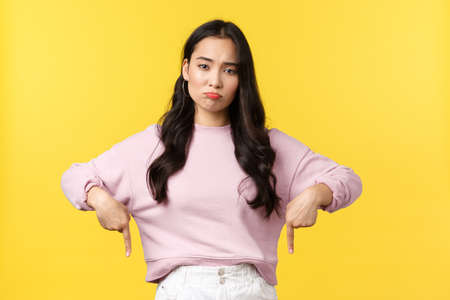 People emotions, lifestyle and fashion concept. Disappointed moody asian girl pointing fingers down and grimacing unsatisfied as showing bad product, complaining, standing yellow background