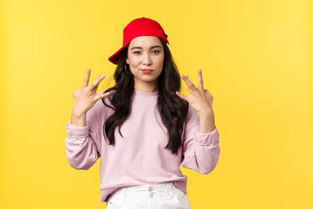 People emotions, lifestyle leisure and beauty concept. Stylish and cute hip-hop dancer girl, showing swag gesture and smirk sassy, acting confident and cool, standing yellow background
