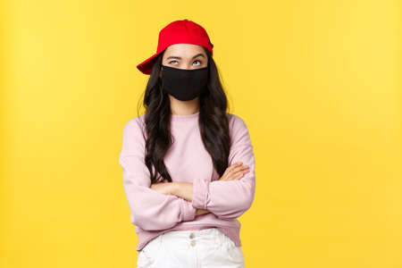 Covid-19, social-distancing lifestyle, prevent virus spread concept. Thoughtful and creative cute asian girl in red cap and face mask, looking up thinking and smiling with eyes, cross arms chest