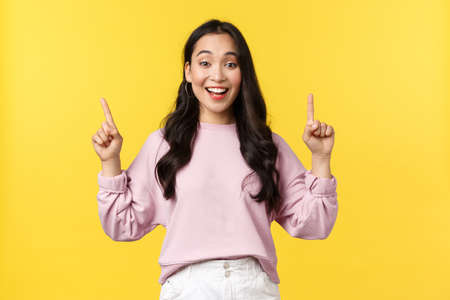 People emotions, lifestyle and fashion concept. Smiling female student showing summer vacation offers, special promo or discounts at store, pointing fingers up and smiling, yellow background 版權商用圖片