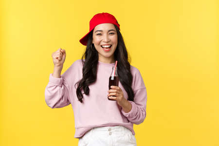 People emotions, drinks and summer leisure concept. Enthusiastic happy asian girl enjoying her soda, drinking beverage and dancing, smiling cheerful, standing yellow background 版權商用圖片