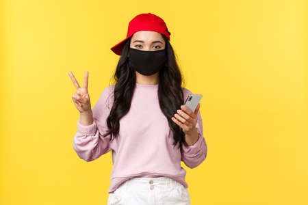 Covid-19, social-distancing lifestyle, prevent virus spread concept. Cute teenage asian girl in protective face mask and red cap, meeting friends on summer weekend, using smartphone, make peace sign