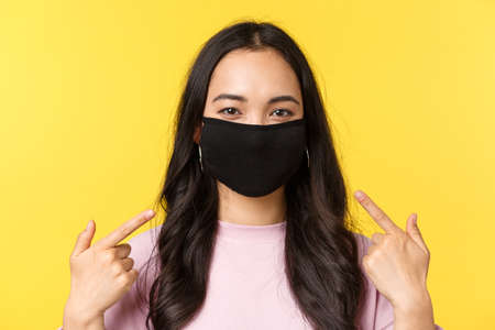 Covid-19, social-distancing lifestyle, prevent virus spread concept. Asian cheerful girl, smiling and pointing at face mask, recommend wearing protective measures during coronavirus pandemic 版權商用圖片