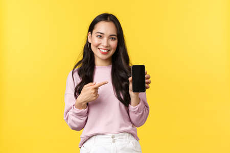 People emotions, lifestyle leisure and beauty concept. Smiling asian woman 20s, showing smartphone display, recommend application or mobile game, pointing finger at screen, yellow background 版權商用圖片