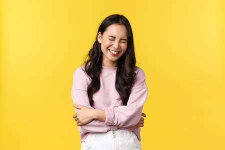 People emotions, lifestyle and fashion concept. Happy carefree smiling asian woman chuckle, touch belly and laughing out loud, standing yellow background, hear good joke 版權商用圖片