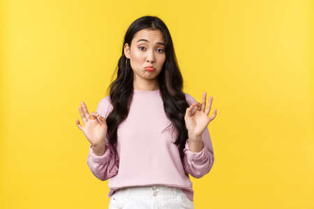People emotions, lifestyle and fashion concept. Pleased and impressed asian girl nod in approval, pouting and show okay gesture, well played, not bad, standing satisfied yellow background