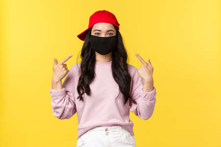 Covid-19, social-distancing lifestyle, prevent virus spread concept. Smiling attractive asian girl during coronavirus, pointing at face mask to recommend go outside in it, yellow background