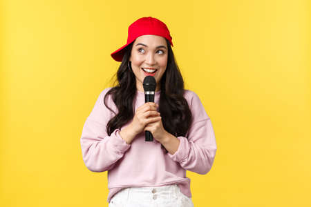 People emotions, lifestyle leisure and beauty concept. Dreamy and cute asian girl in red cap, looking upper left corner happy with broad smile, perform stand-up or give speech, singing in microphone