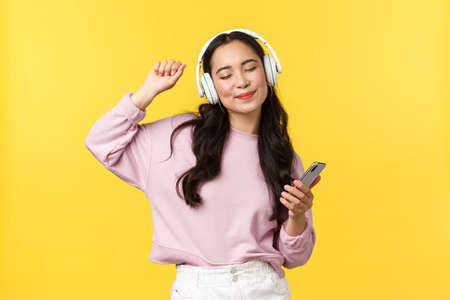 People emotions, lifestyle leisure and beauty concept. Carefree good-looking asian woman close eyes and dancing relaxed with smartphone, listening music in wireless headphones