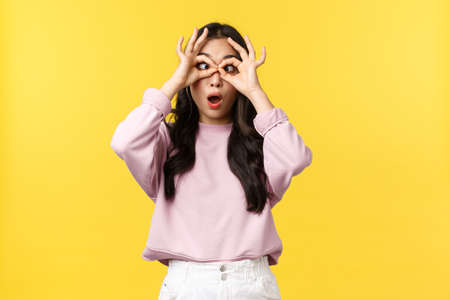 Lifestyle, emotions and advertisement concept. Funny and playful cute asian girl fooling around, make fake glasses with hands over eyes and squinting, showing tongue, standing yellow background 版權商用圖片