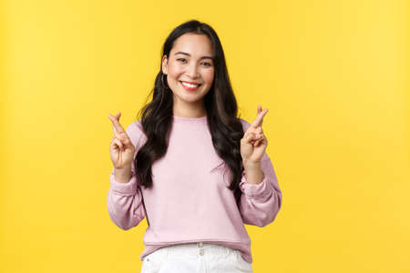People emotions, lifestyle and fashion concept. Hopeful and optimistic cute asian girl having high hopes, cross fingers good luck and smiling, making wish, standing yellow background