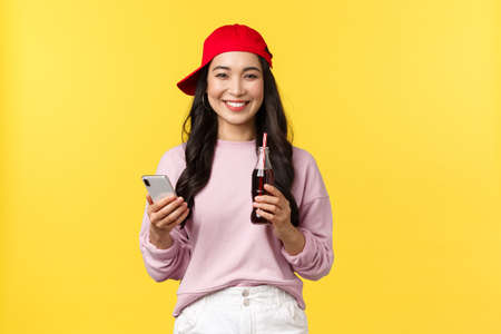 People emotions, drinks and summer leisure concept. Young teenage korean girl in red cap, messaging, using smartphone and drinking soda beverage, standing yellow background pleased 版權商用圖片