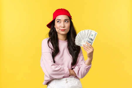 People emotions, lifestyle leisure and beauty concept. Thoughtful stylish korean girl in cap, looking up as thinking where go summer vacation, holding money, earned lots of cash on freelance
