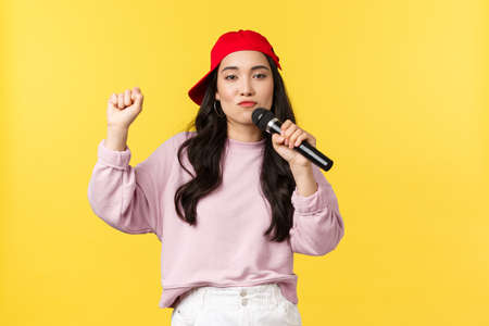 People emotions, lifestyle leisure and beauty concept. Carefree funny asian girl in red cap dancing and singing in microphone, performing hip hop song, standing yellow background