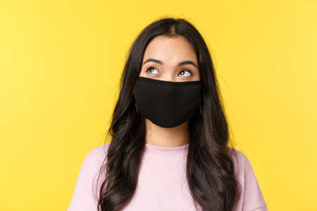 Covid-19, social-distancing lifestyle, prevent virus spread concept. Dreamy and thoughtful asian girl in face mask, looking upper left corner thinking, standing yellow background 版權商用圖片