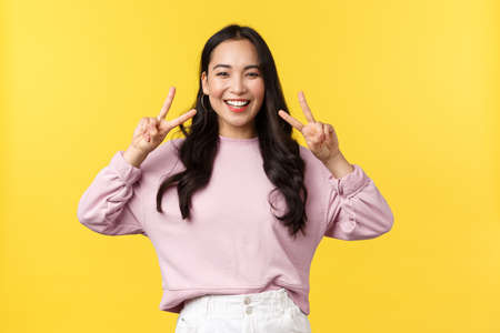 People emotions, lifestyle and fashion concept. Cheerful kawaii asian girl in stylish outfit showing peace sign and smiling upbeat with white teeth, standing over yellow background, enjoy summer