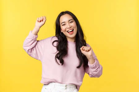 People emotions, lifestyle leisure and beauty concept. Upbeat happy and cheerful asian girl dancing and having fun, partying, moving rhythm music and smiling over yellow background