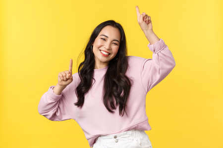People emotions, lifestyle leisure and beauty concept. Happy carefree attractive korean girl having fun on party, dancing and enjoying summer, raise hands up, smiling broadly, yellow background
