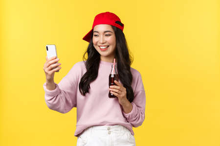 People emotions, drinks and summer leisure concept. Stylish cute asian female blogger in red cap, taking selfie with smartphone, drinking soda beverage and photographing herself