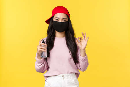 Covid-19, social-distancing lifestyle, prevent virus concept. Cute asian female in face mask and red cap, showing okay sign as advice use hand sanitizer, recommend hygiene measures on coronavirus