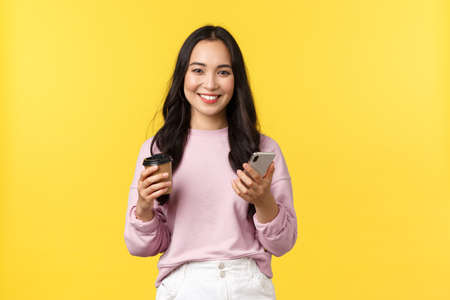 People emotions, lifestyle leisure and beauty concept. Attractive female student, college girl drinking takeaway coffee and checking messages on mobile phone, smiling at camera 版權商用圖片